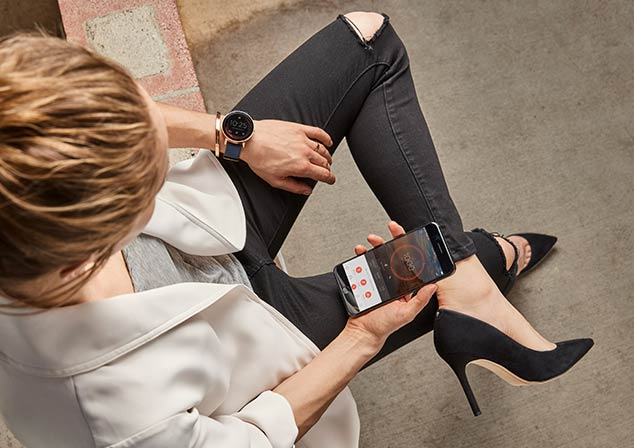A woman wears a misfit vapor smartwatch while looking at the misfit app