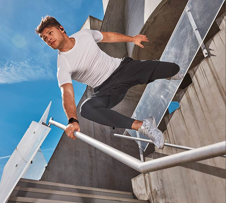 A man jumping over a stair railing with a misfit smartwatch on his wrist.